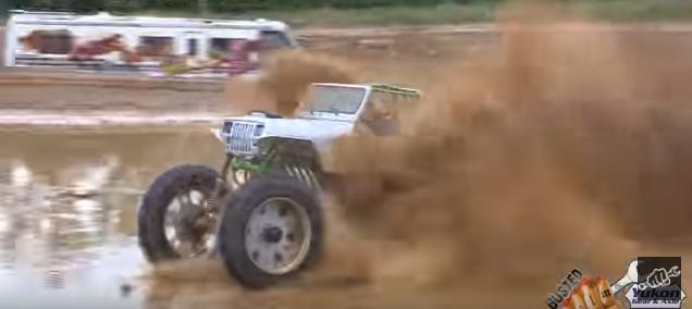 An 8,000 pound farm Jeep skims the pond and kicks up some mud