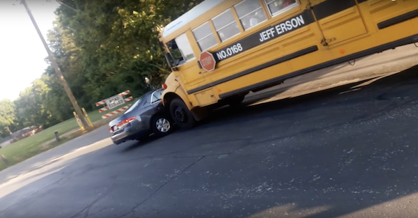 School bus loaded with kids drags a Honda across the parking lot