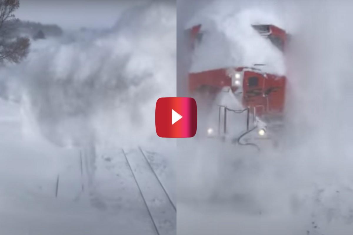 train blasts through snow drift