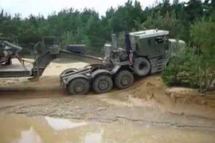 Off-Road Military Trailer Hauls Tank Through Rough Terrain