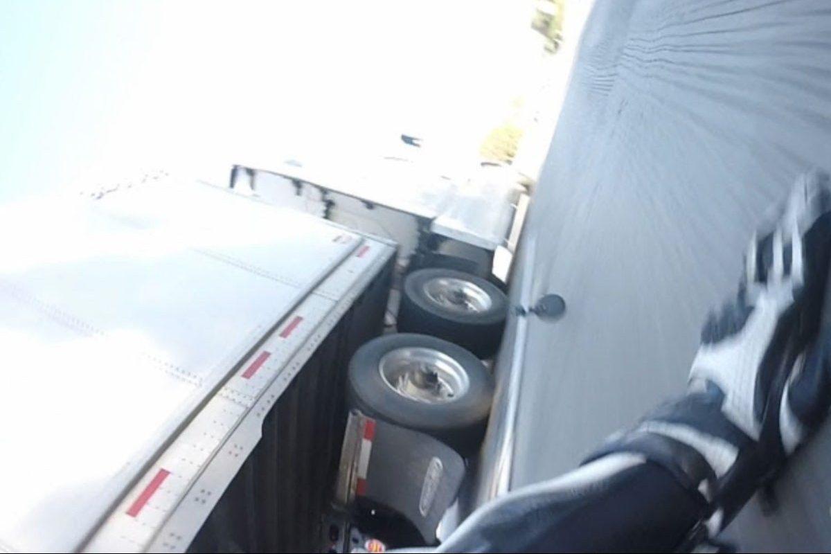biker slides under semi