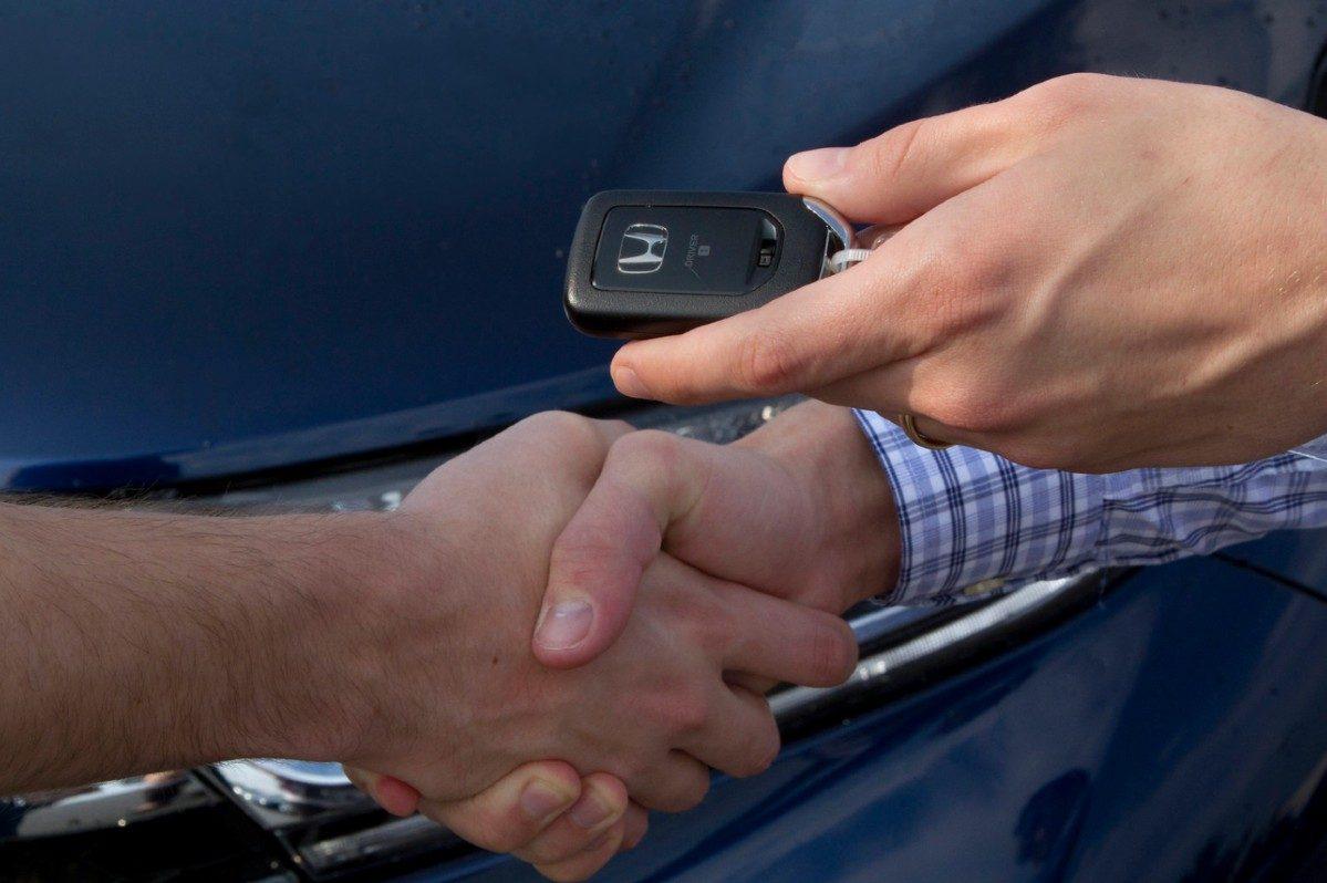 car salesperson handing over keys