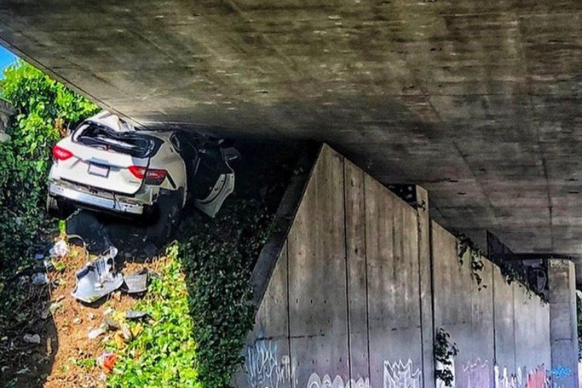 maserati wedged under overpass