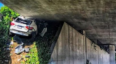 maserati wedged under overpass